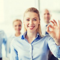 business, people, gesture and teamwork concept - smiling businesswoman showing ok sign with group of businesspeople in office